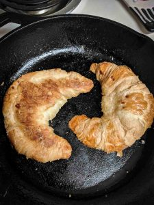 Croissants toasting on a skillet