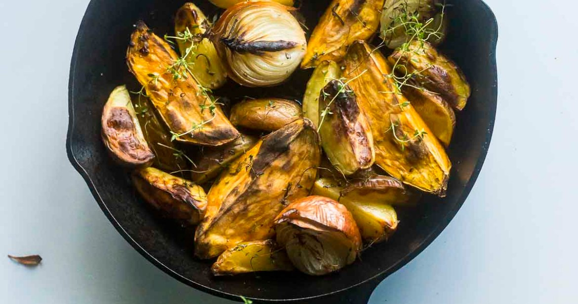 Roast potatoes and onions in a cast iron skillet on table