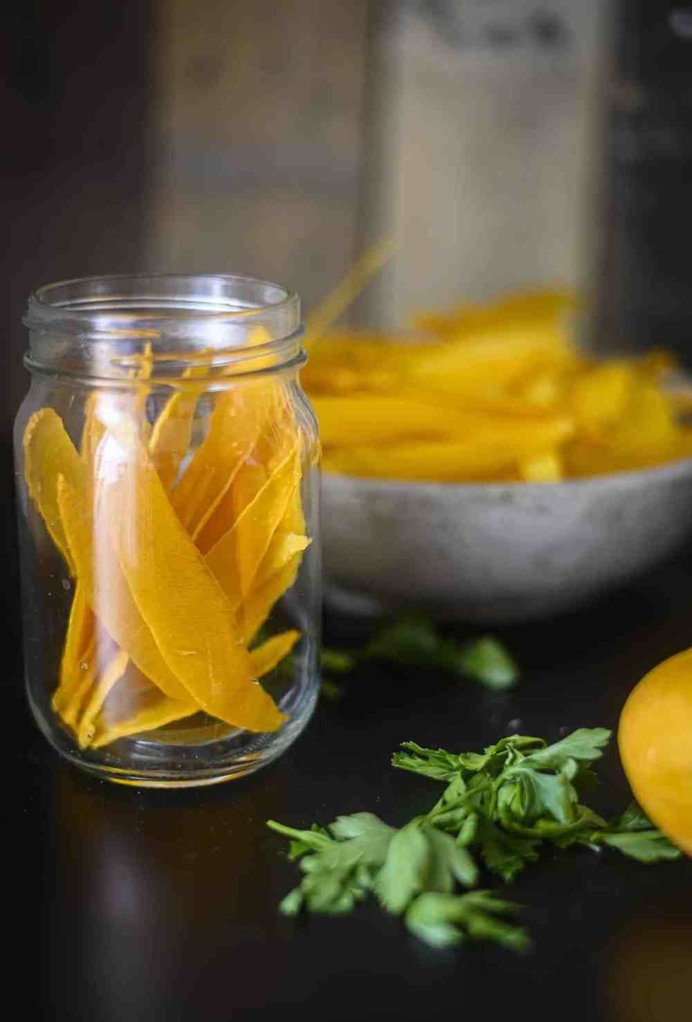 Mango chips in a glass jar on table