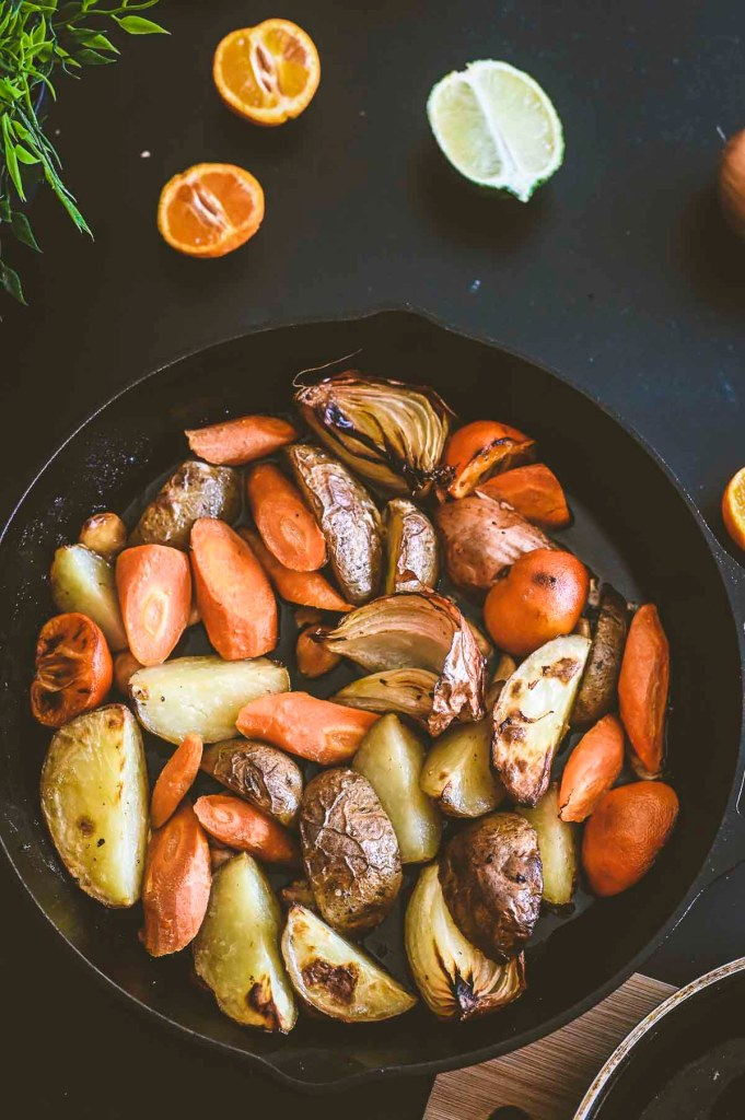 cast iron skillet with roast potatoes, carrots, and onions