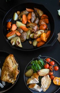 Roast Chicken on table with pan full of roast vegetables
