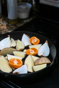 Onions, potatoes, and mandarins in pan