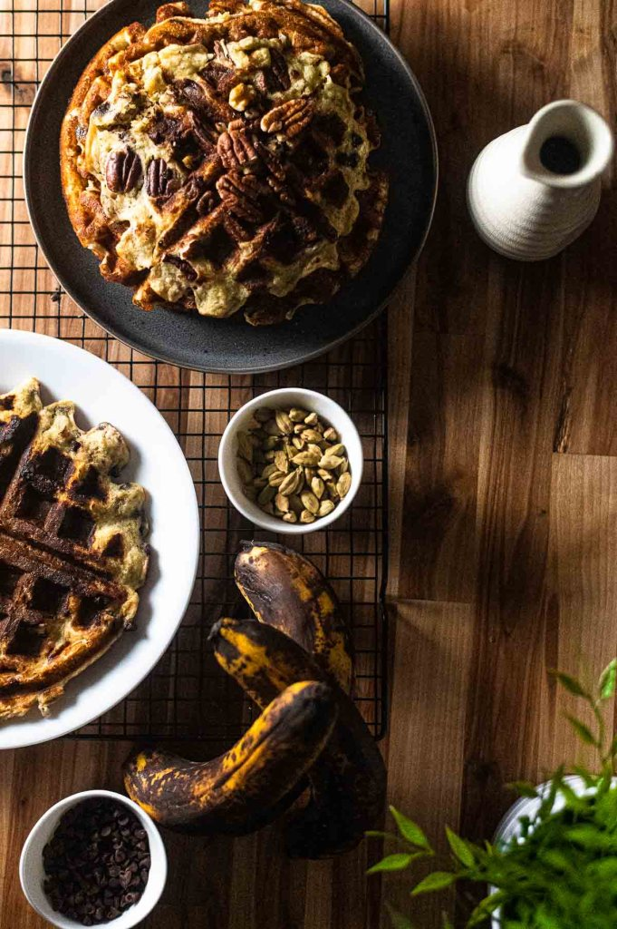 overhead waffles on table with cardamom syrup bottle with