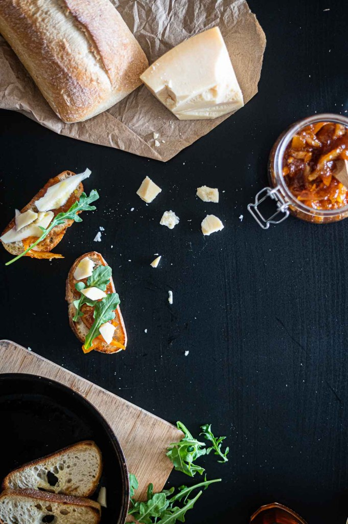 Old fashioned orange marmalade with open faced sandwiches on table