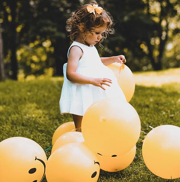 bambina con palloncini gialli