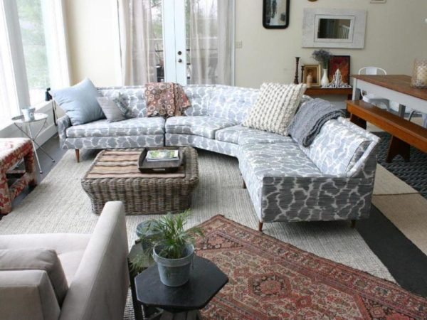 patterned-pale-blue-circular-sectional-sofa-bed-with-a-rattan-coffee-table-and-a-moroccan-rug-in-a-living-room
