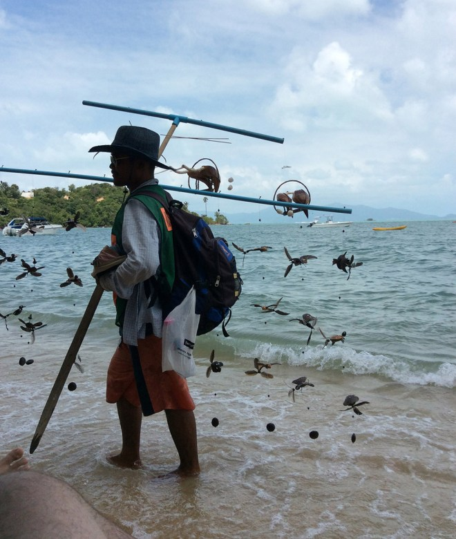 A beach vendor selling bird wind chimes in Bo Phut