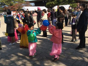 Kids play with balloons while watching the Korean dance performance