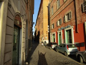 """The afternoon sun made the bright earth tones of Rome's buildings glow as we crossed the Ponte Sisto bridge. I especially liked the cast of the long shadows, including the """"BAR"""" sign on the wall opposite the alley."""
