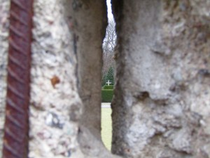 A cross commemorating the graves of St. Elizabeth Cemetery that were displaced by the building of the Berlin Wall seen through a crack in the wall.