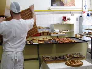 A baker at Biscottificio Artigiano Innocenti takes a sheet of cookies out of the conveyor belt oven.