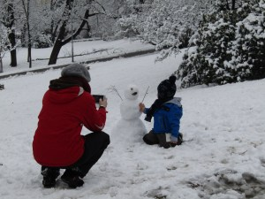 A young boy puts the finishing touches on a snowman in Riegrovy Sady.