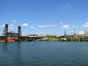 Looking east over the Willamette River toward the Steel Bridge, Moda Center—home to the NBA's Portland Trail Blazers—and the glass towers of the Oregon Convention Center.