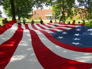 During the park ranger-led Flag Talk, participants unfurl and hold a replica of the garrison flag that flies above Fort McHenry. At 30 feet by 42 feet, it required more than 30 people to hold it steady.