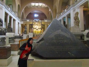 Guide Asmaa next to the capstone carved with a phoenix bird, which is a part of an ancient creation story.