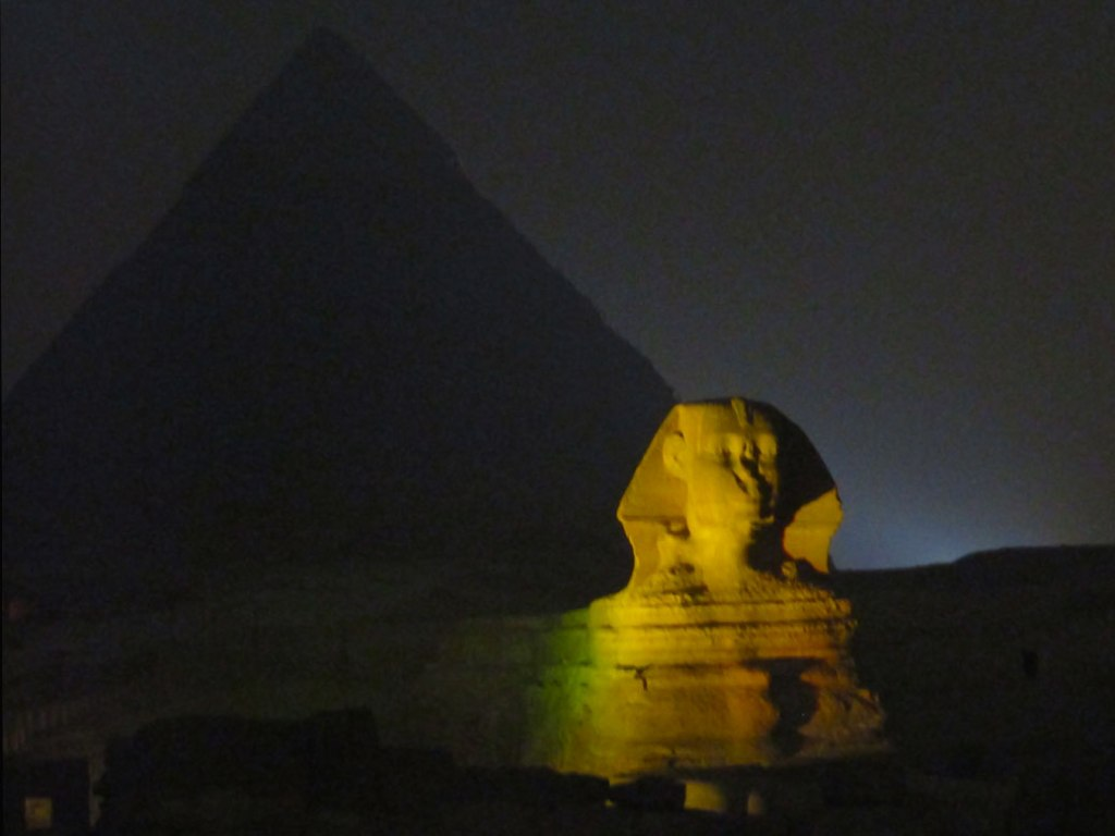 The illuminated Sphinx, with the body of a lion and the head of a person, is quite smaller than the pyramids but still impressive.