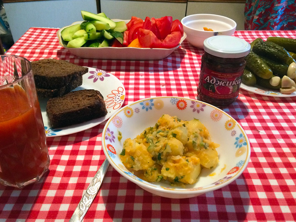 "Herbed potatoes with pumpernickel bread and homemade pickles. The small jar has ""adjika,"" which is a spicy sauce."
