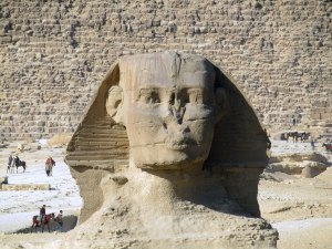 Close up of the Sphinx's face with a pharaoh's headdress and missing nose. Look how tiny the horseback riders are in comparison!