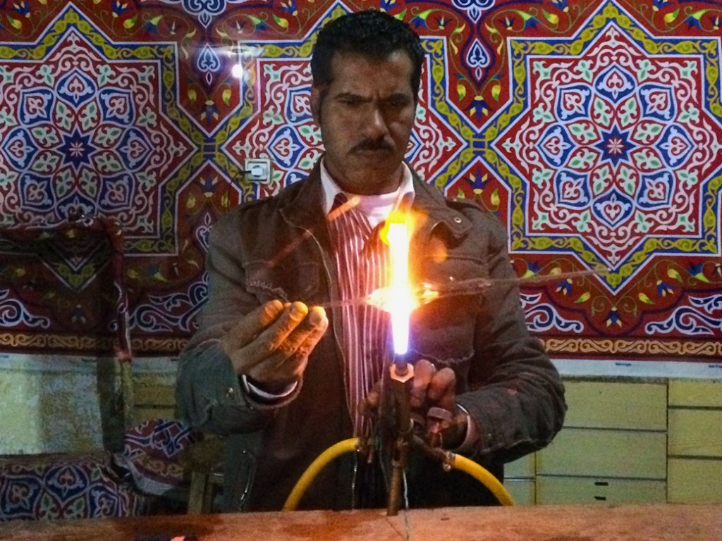 Outside the Alfayed Perfume Co. in Aswan, a man hand makes the perfume bottles used in the store.