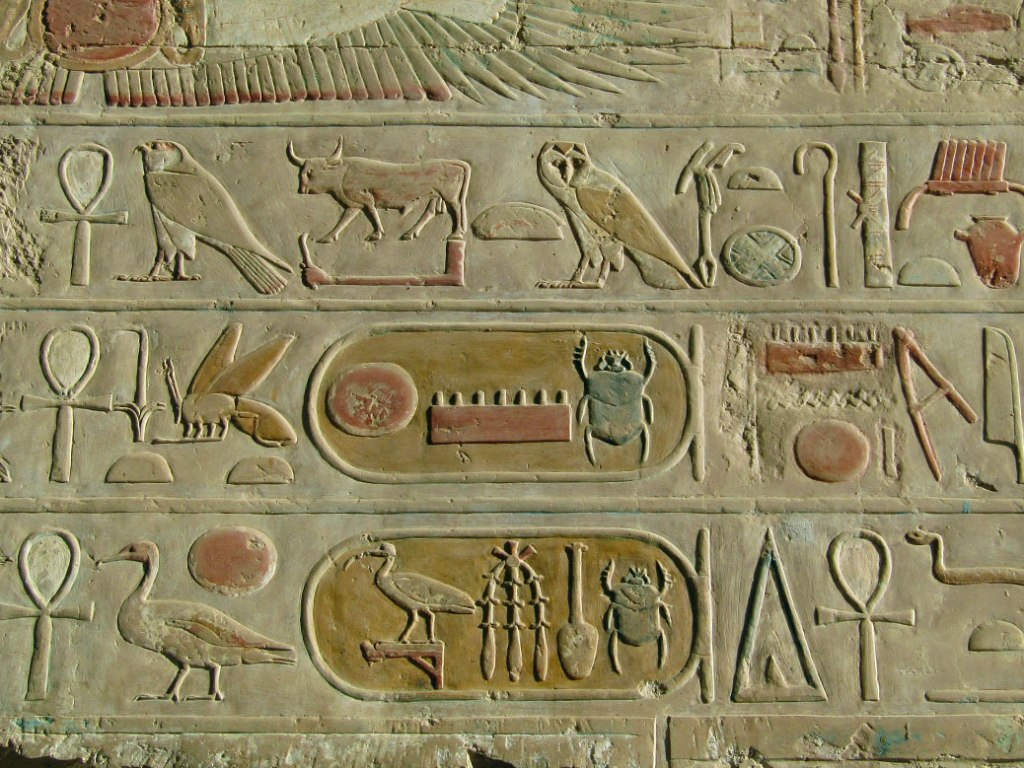 Enclosed hieroglyphics in the Temple of Hatshepsut. Known as cartouche, they indicate a name and the beetle (scarab) usually denotes the name of a pharaoh. The top shows the name of Pharaoh Thutmose III, nephew/stepson and heir to Hatshepsut.