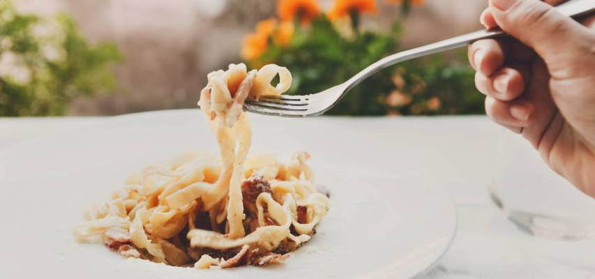 Eating pasta. Fork closeup. Traditional italian carbonara with bacon, egg and parmesan decorated with basil on white round plate at wooden table. Restaurant food, selective focus
