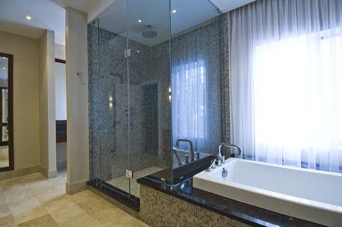 this beautiful bathroom by biglarkinyan design partnershop has a shower and adjacent bathtub design found in many high end bathrooms
