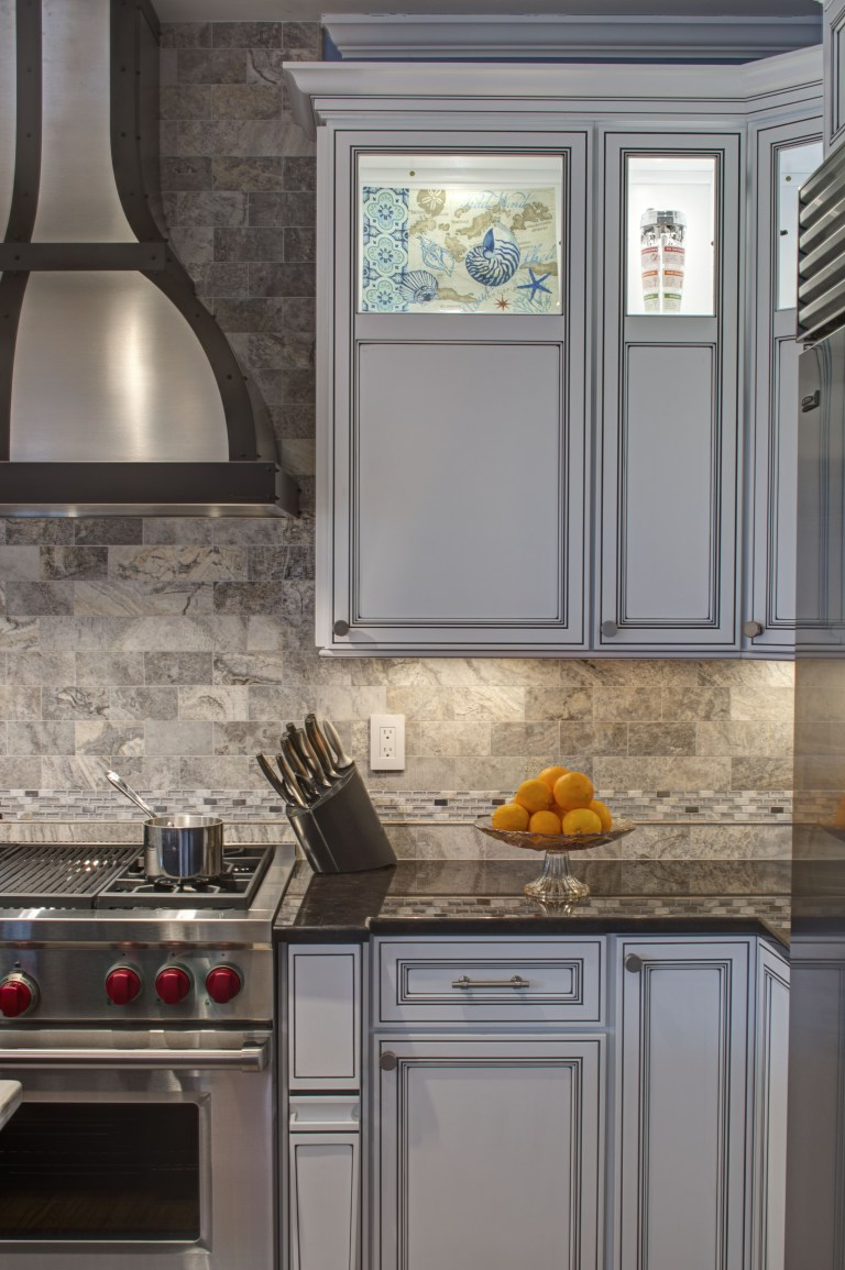 traditional style white cabinetry stainless steel gas range and hood partial glass doors on upper cabinets backsplash tile to ceiling