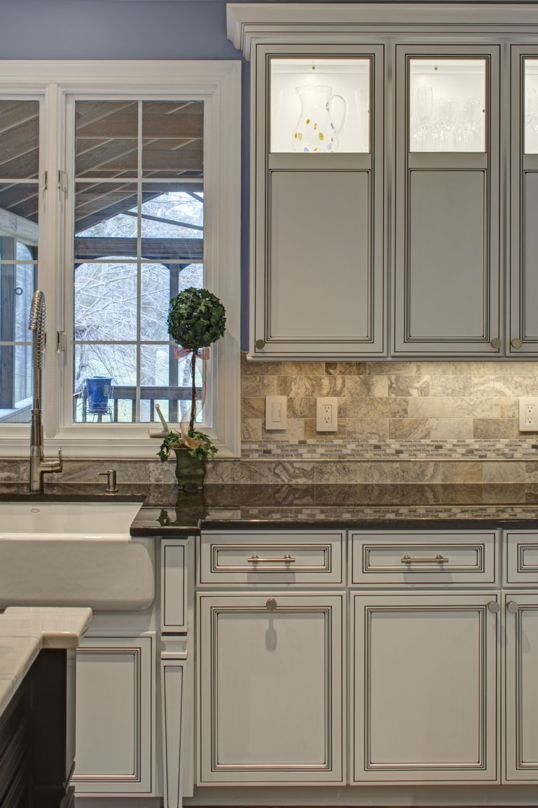 traditional style white wood cabinetry window over porcelain apron sink looks out to screened in porch