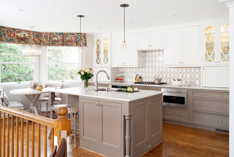 bright kitchen neutral color palette gray toned lower cabinetry white uppers wood floors island with pendant lighting