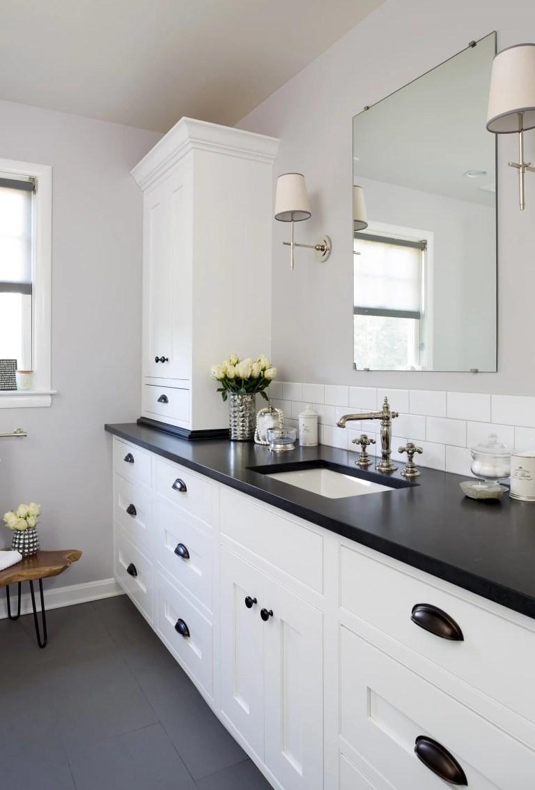 black and white bathroom with plenty of storage subway tile backsplash sconce lighting