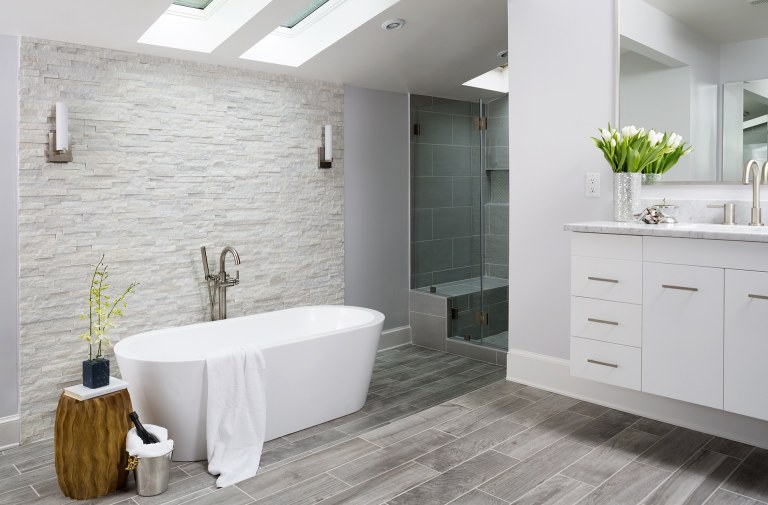 modern bathroom freestanding tub tile floors look like wood textured stone feature wall skylight gray color palette