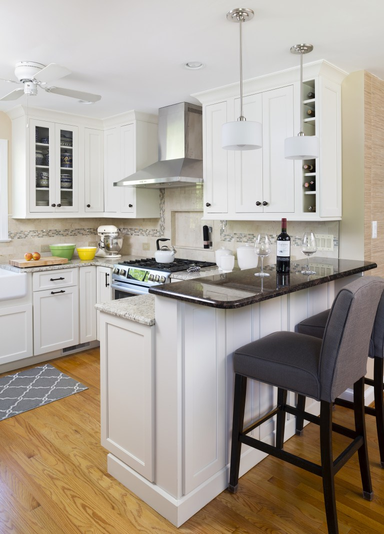 beige and white kitchen with wood floors peninsula with seating and pendant lighting above