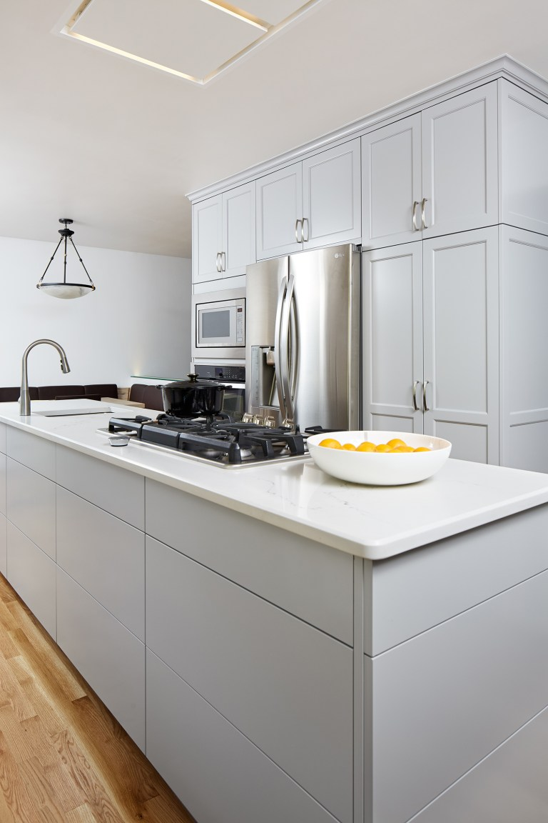 kitchen with white cabinetry and countertops stovetop and sink in island