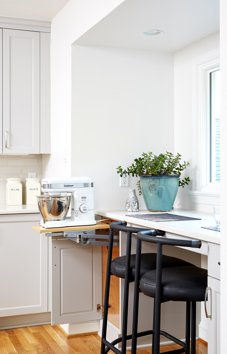 white kitchen with bar height seating in front of window