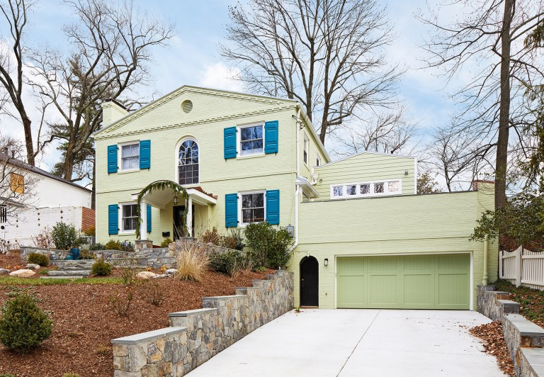front porch renovation on DC home blue shutters stone walkway green garage doors