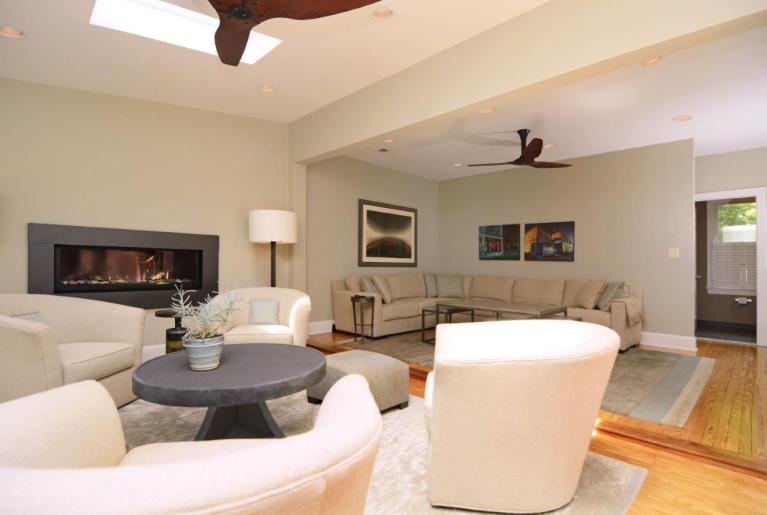 renovated living area white walls and skylight light wood floors and modern fireplace