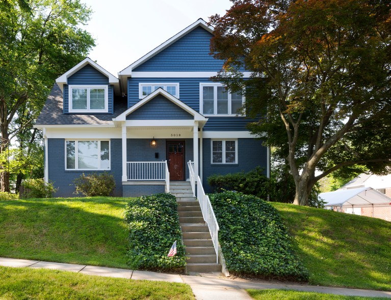 blue maryland house on hill with stone stairs and covered front porch
