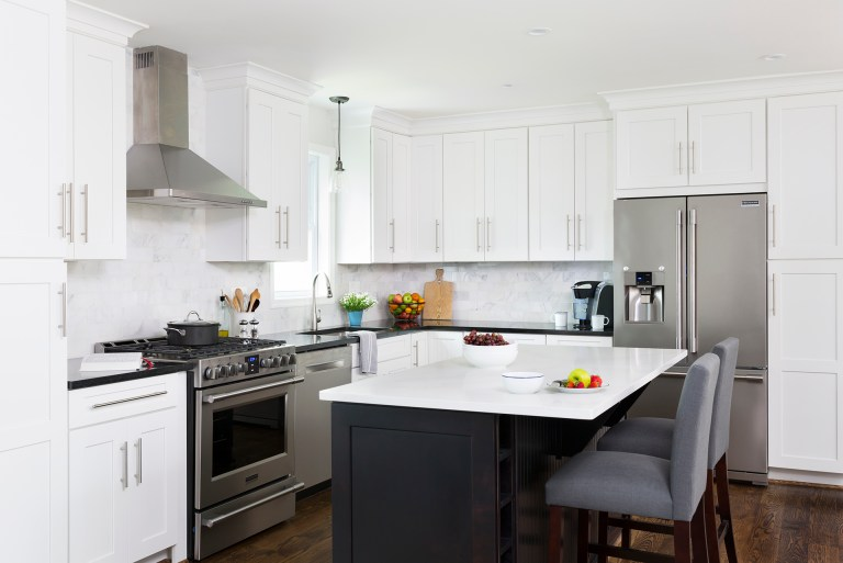 kitchen with white cabinetry and stainless steel appliances navy blue island cabinetry seating at island