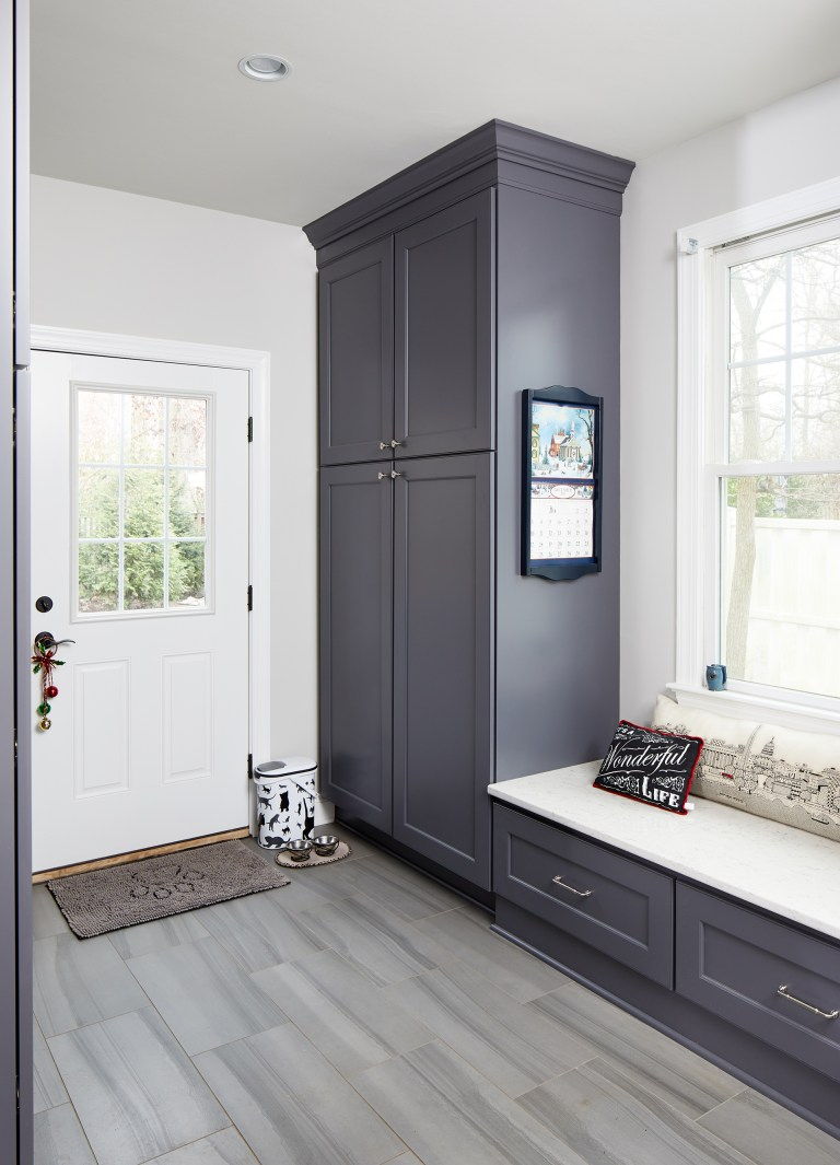 mudroom with grayish blue cabinetry plenty of storage and built in bench under window