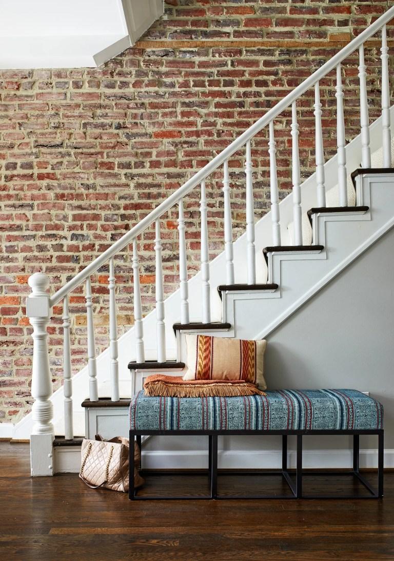 exposed brick wall in entryway along staircase dark wood floors