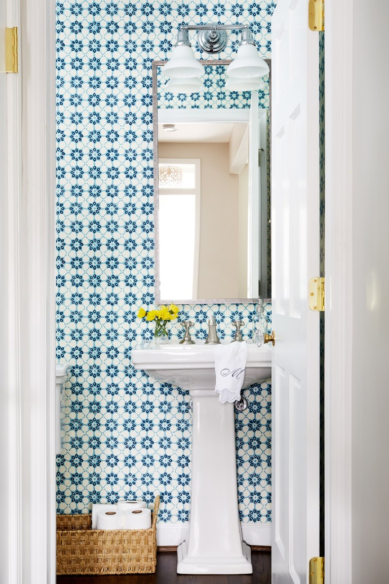 first floor powder room with pedestal sink, wood floors, and teal geometric wall tile