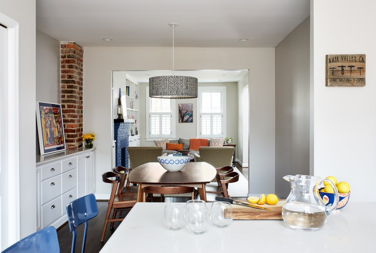 view from kitchen into dining and living area white cabinetry and exposed brick column