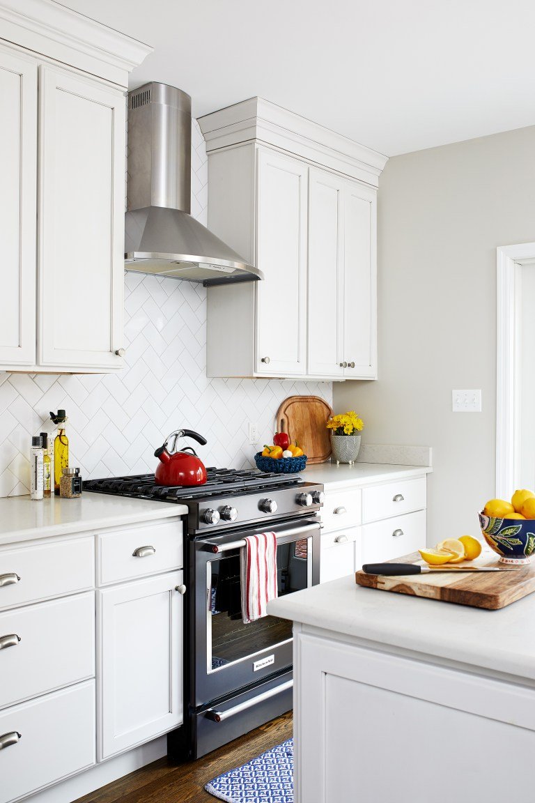 white cabinetry black stainless gas range with stainless steel hood