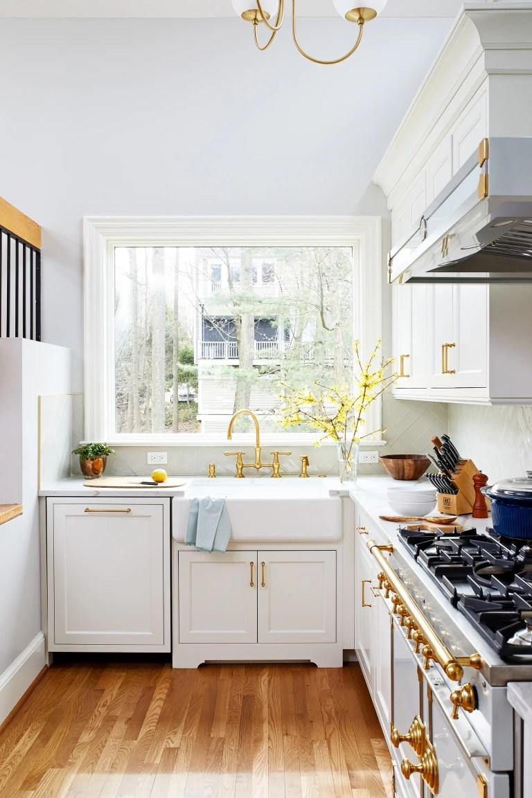 kitchen with large window over farmhouse sink white cabinetry paneled dishwasher