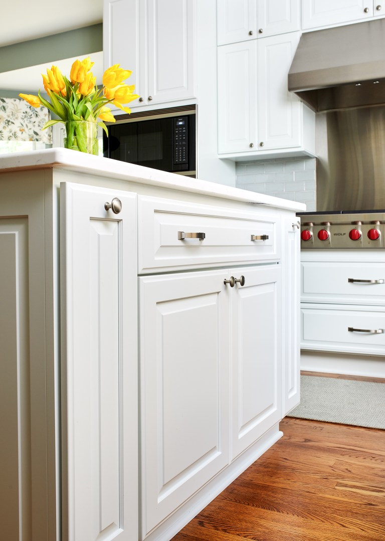 kitchen island with white cabinetry and brushed chrome hardware