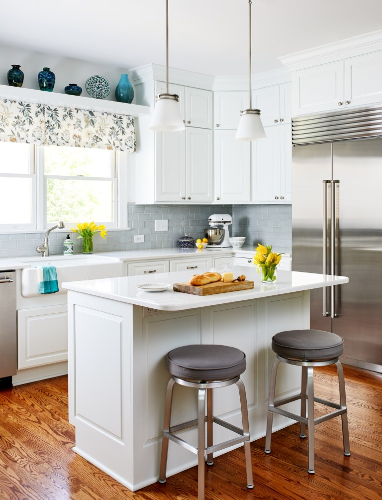 white kitchen with island seating and pendant lighting open display shelf above window