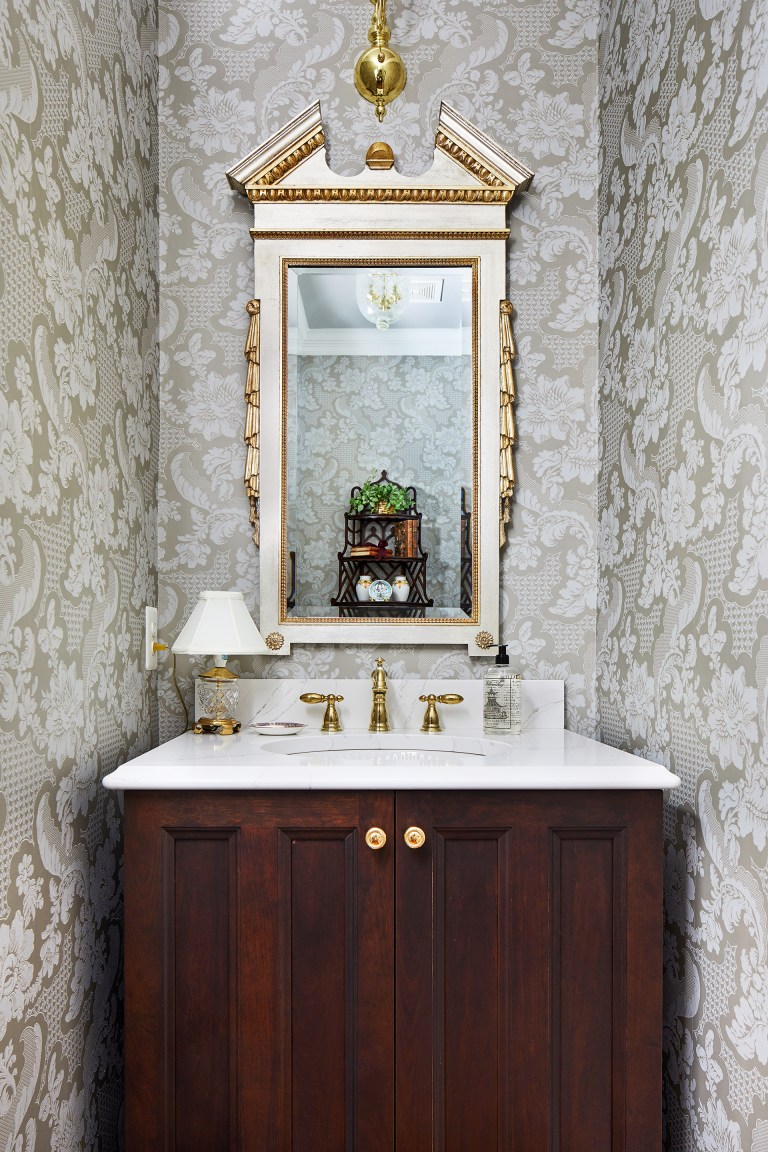 vanity with two doors and gold knobs, white marble top with gold faucets, gold rectangle mirror