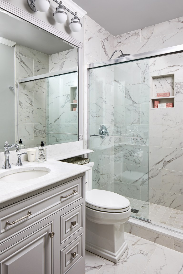 white and grey bathroom with marble shower walls and semi-frameless shower doors