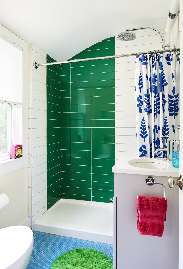green and white tile bathroom with one sink vanity and mirror