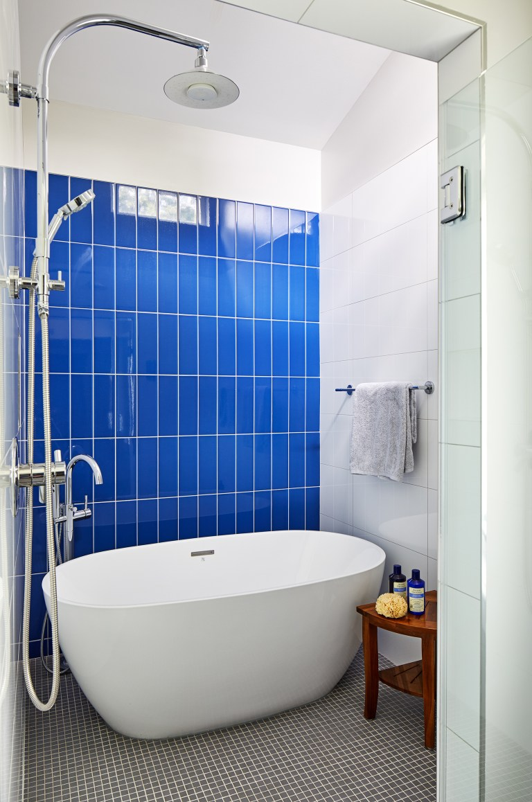bathroom with white tub and white and blue tiles